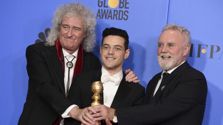 Brian May (l) und Roger Taylor (r) von der Band Queen freuen sich mitRami Malek, der für