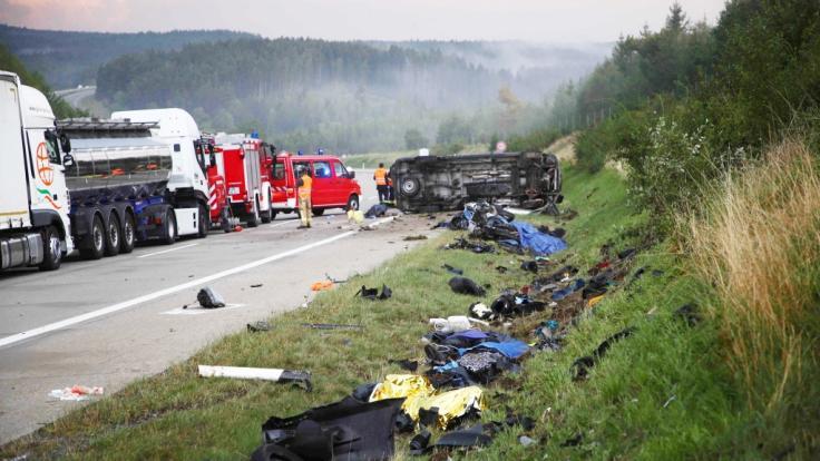 Trümmerteile liegen an der Seite der Autobahn 9 an der Unfallstelle, im Hintergrund liegt ein Fahrzeug auf der Seite.