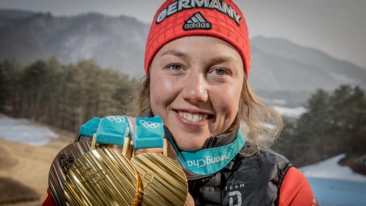 Laura Dahlmeier zeigt stolz ihre drei olympischen Medaillen.