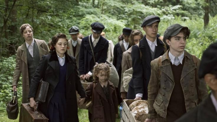 Helga (Nina Proll, li.), Betty (Sophie Stockinger, 2. v. li.) und die kleine Milli (Amy Lee Wörgötter) fliehen mit anderen Kindern und Jugendlichen vor den Nazis.