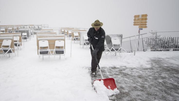 Ein Mann räumt den Neuschnee weg, der auf der Terrasse der Bergstation am Stanserhorn (Schweiz) in 1851 Meter Höhe liegt. Eine Kaltfront hatte den Schnee gebracht. (Foto)