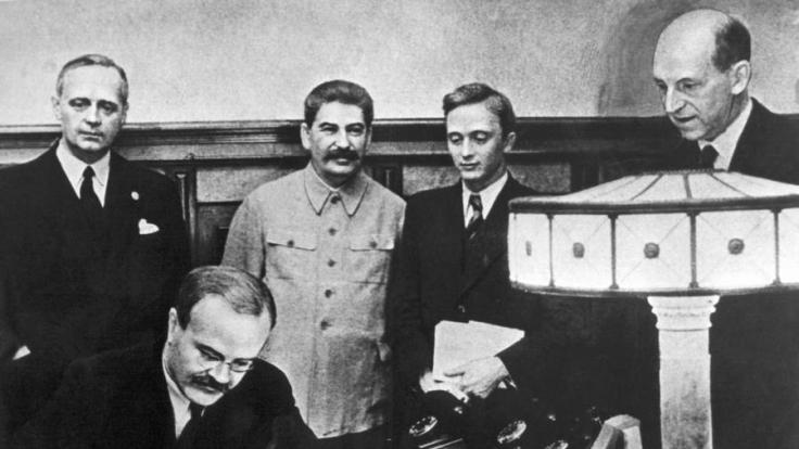 Die Außenminister Wjatscheslaw Molotow (vorn) und Joachim von Ribbentrop (l.) unterzeichnen den Pakt. (Foto)