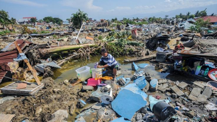 Indonesien, Palu: Agustin (51) wäscht nach dem Erdbeben Wäsche zwischen den Ruinen seines Hauses im Dorf Balaroa. (Foto)