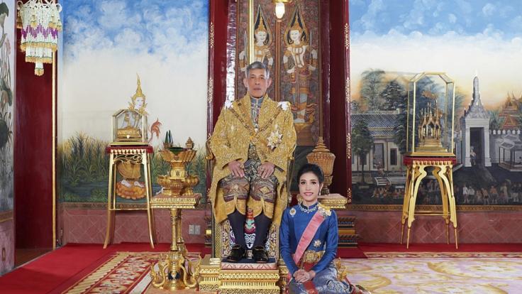 König Maha Vajiralongkorn von Thailand sitzt auf seinem Thron, während neben ihm Sineenat Wongvajirapakdi kniet. (Foto)