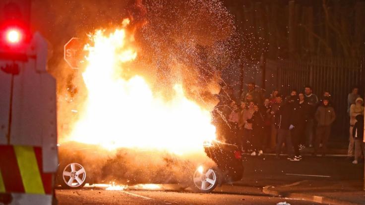 Ein entführtes Auto steht während sozialer Unruhen in Flammen.